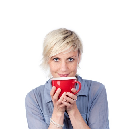 hands cupped: Young blond woman holding red coffee cup against white background