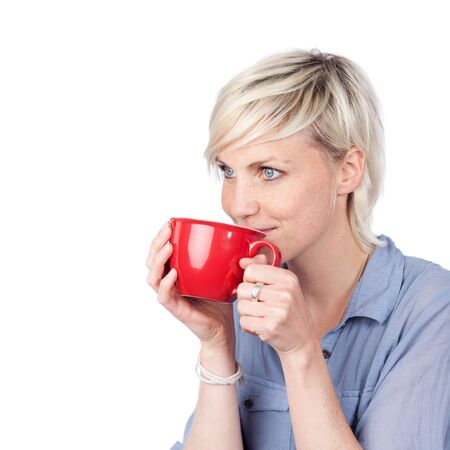 addictive drinking: Thoughtful young blond woman drinking against white background