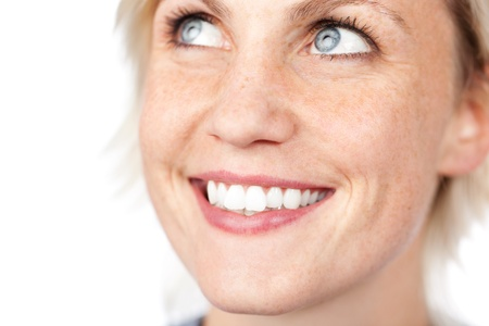 Extreme closeup of a beautiful blue eyed woman smiling against white background photo