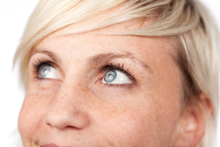 freckles: Coseup of a beautiful blue eyed woman looking up against white background