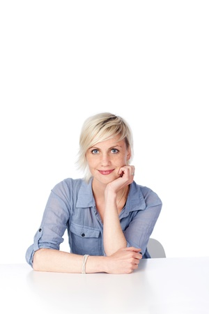 one mid adult woman: Portrait of a confident blond woman with hand on chin sitting at table against white background