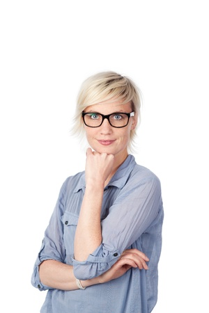 contemplative: Portrait of a young blond woman in blue shirt standing with hand on chin against white background