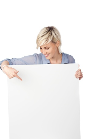 Young blond woman pointing at white sign against white background photo