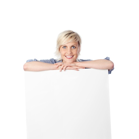 Happy young blond woman leaning on white sign against white background photo