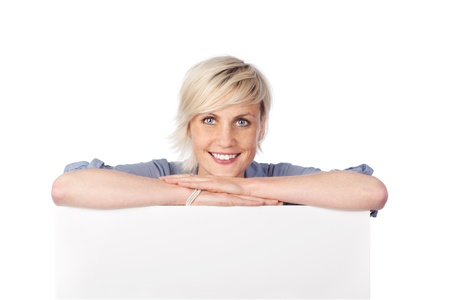 Young blond woman leaning on white sign against white background photo