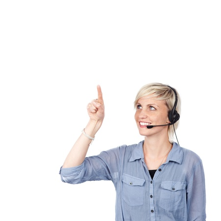 woman pointing up: Smiling young woman with headset pointing up against white background