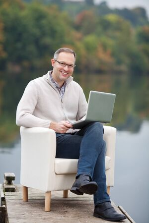 Full length portrait of happy mature man using laptop while sitting at pier photo