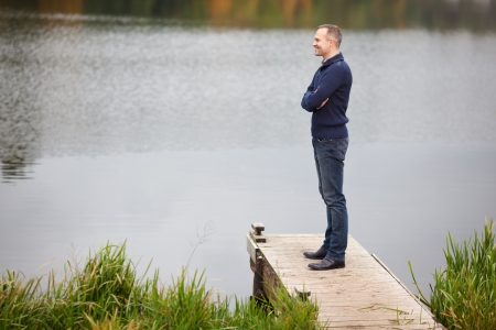 profile views: Profile shot of mature man with arms crossed standing on pier while looking at lake