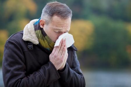 風邪に苦しんでのジャケットを着て成熟した男 写真素材