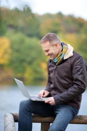 40 years old: Happy mature man using laptop while sitting on fence Stock Photo