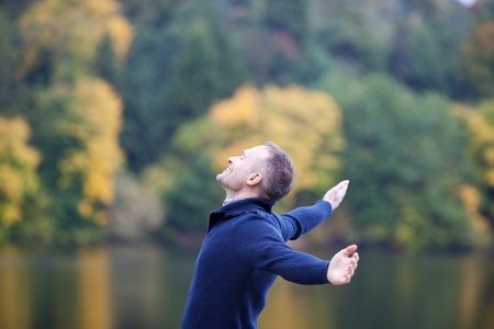 arms wide: Side view of smiling mature man with arms outstretched standing on pier Stock Photo