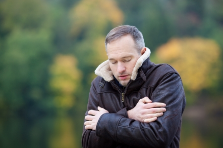wintery day: Mature man in jacket shivering outdoors