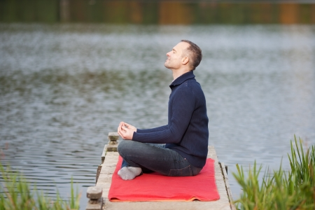 side: Profile shot of mature man meditating in lotus position on pier against lake Stock Photo