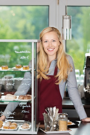 catering service: friendly waitress leaning on coffee shop counter