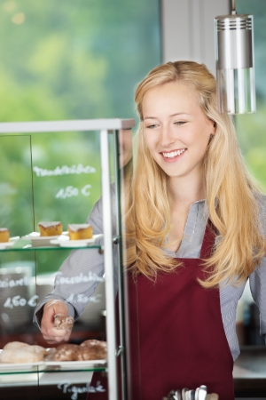 selling service smile: young blonde woman working in a cafe