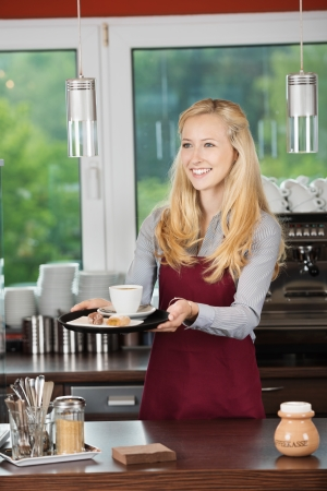 salesgirl: Happy waitress serving coffee with sweet food at counter