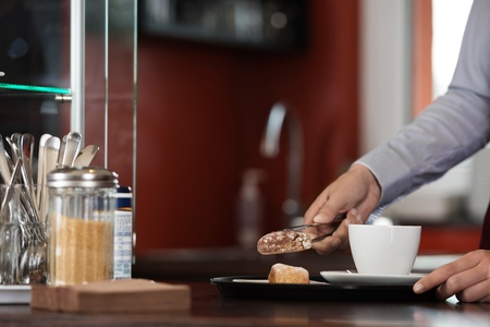 keeping: Cropped image of waitress keeping biscuit in tray at coffee shop counter