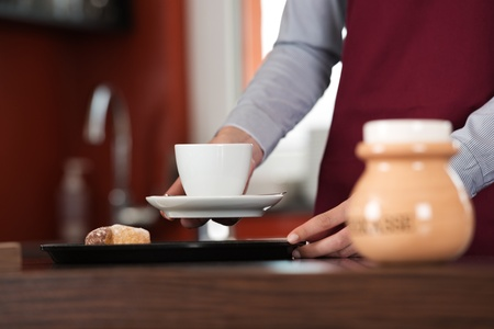 waitress serving a cup of coffee on a tray photo