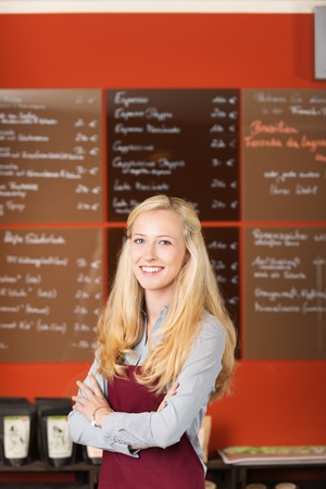 saleslady: confident waitress standing in cafe with crossed arms Stock Photo