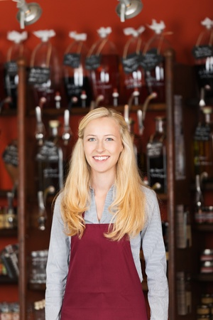 cheerful saleswoman with apron standing in gourmet store Stock Photo - 21266525