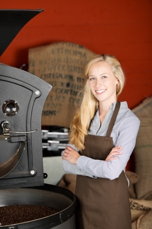 smiling blond woman producing roasted coffee beans photo