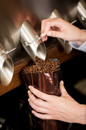 packaging equipment: close-up view of a woman filling coffee beans in bag
