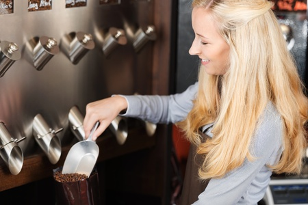 beautiful woman filling coffee beans in a bag Stock Photo - 21266585