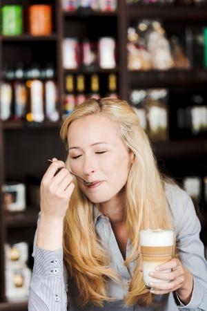 cheerful woman enjoying latte macchiato at cafe photo