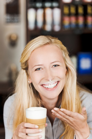 smiling blond woman with milk foam at her face photo