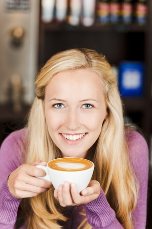 addictive drinking: smiling blond woman drinking cappuccino in cafe