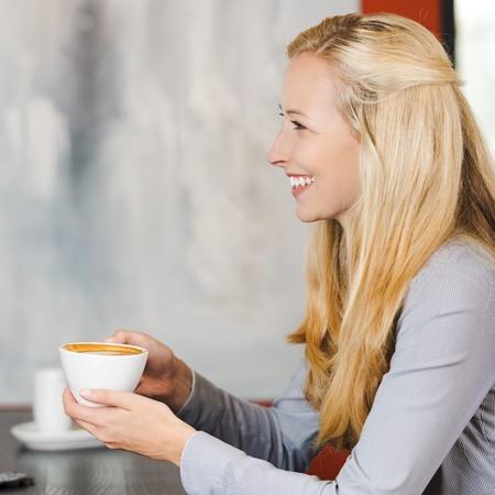 smiling blonde woman enjoying cappuccino at cafe photo