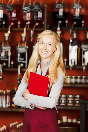 Portrait of confident waitress holding book in cafe photo