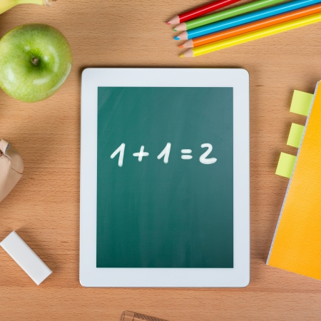 slate: Digital tablet on a school desk with math exercise between a paper notebook, pencils, an eraser, and an apple