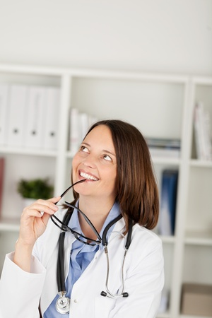 Thoughtful female doctor looking up while holding eyeglasses in office photo