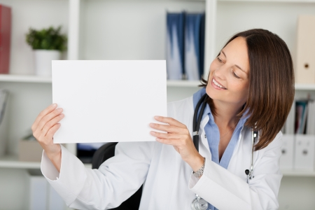 Mid adult female doctor displaying blank placard while looking at it in clinic photo