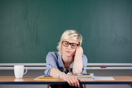 bore: Tired young woman with coffee cup sitting at desk in classroom