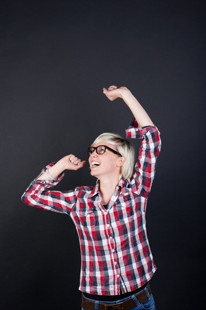 rejoicing: Young woman in chequered shirt rejoicing against black background