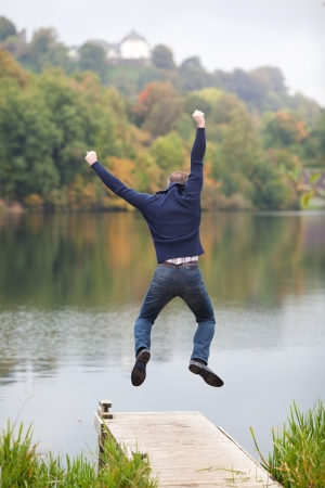 exuberance: Full length of excited man jumping on pier with lake and trees in background Stock Photo