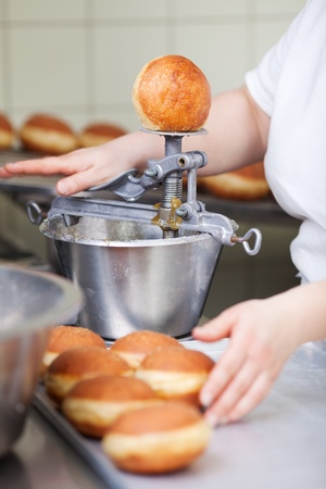 biscuit factory: Baker is filling fried pastry with marmalade Stock Photo