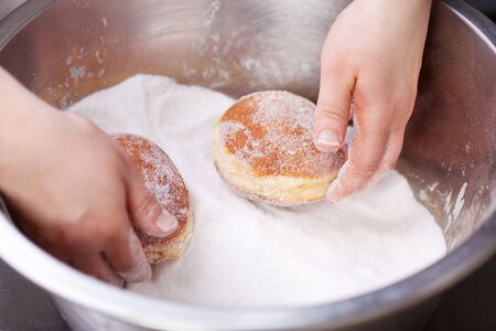 biscuit factory: Baker is rolling doughnuts in container with sugar