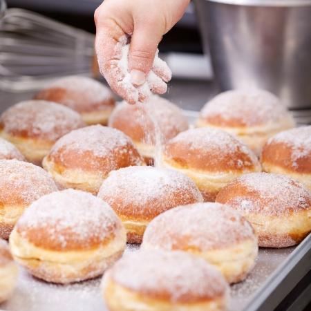 Baker verse le sucre sur la pâte sur une plaque à pâtisserie Banque d'images - 21279064