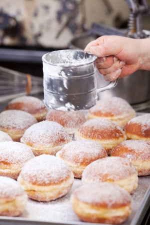 biscuit factory: Baker is poring powdered sugar over doughnuts Stock Photo