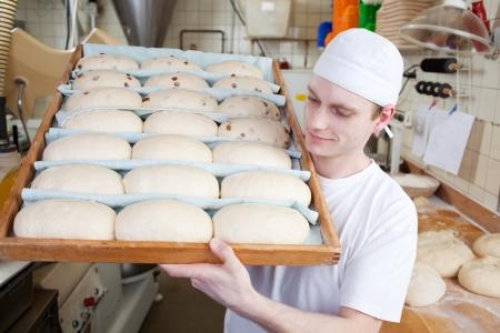 panadero: Panadero pone una tablilla con el pan en un horno en una panadería Foto de archivo