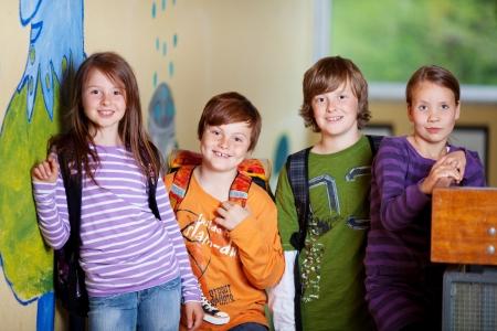 cohesion: Portrait of happy Schoolchildren standing inside the classroom Stock Photo