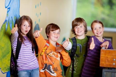 thumbs up group: Studente entusiasta che mostra i pollici in su all'interno della scuola