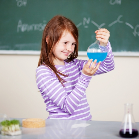 Smiling student holding a chemical formula in chemistry class photo