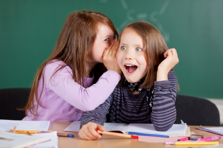 rumours: Two young girls whispering and sharing a secret during class in school Stock Photo