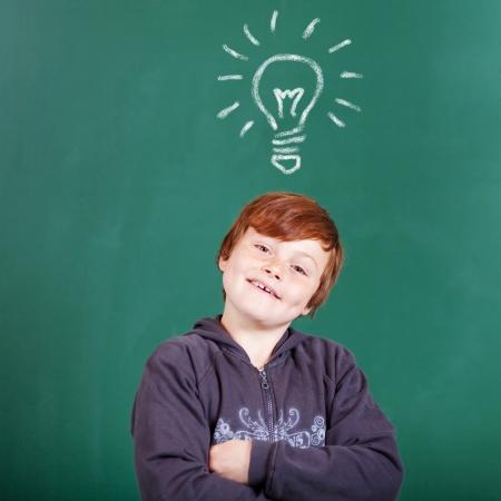 Conceptual portrait of young student thinking a bright idea in blackboard photo
