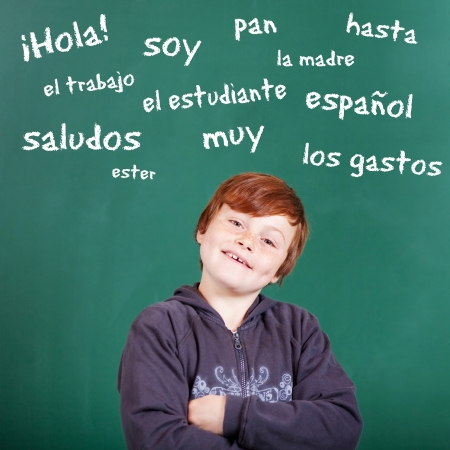 Male student learning Spanish words over the blackboard background