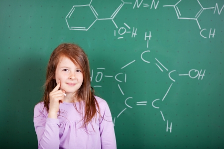 educational problem solving: Pretty female student puzzling a chemistry question standing against a blackboard with a drawing of a chemical formula with a thoughtful expression